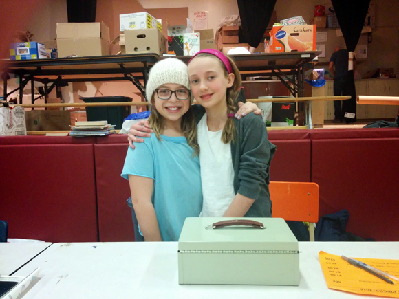 Elmdale students Cleo, 12, and Sophie, 11, help out at the cash table on the opening night of their school's annual BookFest on Feb. 26.