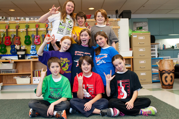 Churchill students show off the different School of Rock t-shirt designs over the years. Photo by Kate Settle