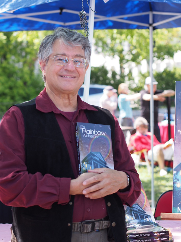 """""""I've sold three books, I'm happy.… there's 150 authors here – some really far out authors – so if I sell 3-5 books today I'm happy,"""" said Martin Bueno, Kitchissippi resident and author of Rainbow Alchemist. Photo by Pearl Pirie."""