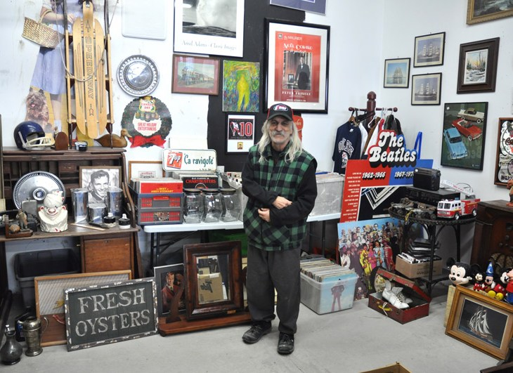 Carl Spano stands in the middle of his antiques store