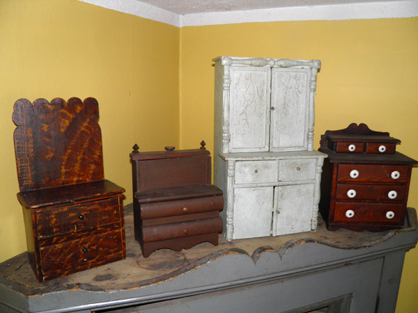"""From left to right: a miniature chest of drawers with scalloped backboard (16""""H / 8.5 W/ 6""""D) from Renfrew County; a sewing stand, (10""""H / 6""""W / 4"""" D) from Western Ontario; white child's china cupboard (24""""H / 13""""W / 9""""D) from Renfrew County; chest of drawers with original porcelain knobs (13""""H / 8.5""""W /12""""D) from Eastern Ontario. Photo courtesy of Shaun Markey"""
