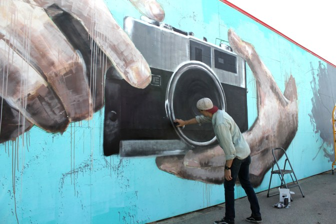 Ryan Smeeton working on his mural at the Canada Science and Technology Museum. Photo submitted by Ryan Smeeton