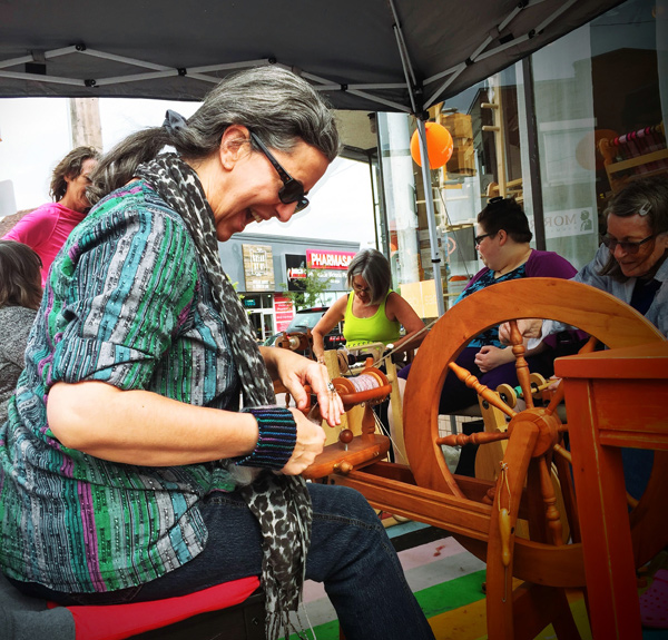 Outside Wabi-Sabi, local knitter Liane Thiry-Smith demonstrates proper wheel technique. They're celebrating International Knitting Day. Not even the impending rain would stop these wool enthusiasts.