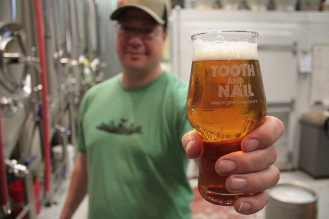 Tooth and Nail Brewing Company's founder Matt Tweedy displays a glass of Rabble Rouser IPA at their combination brewery and pub on 3 Irving Ave.