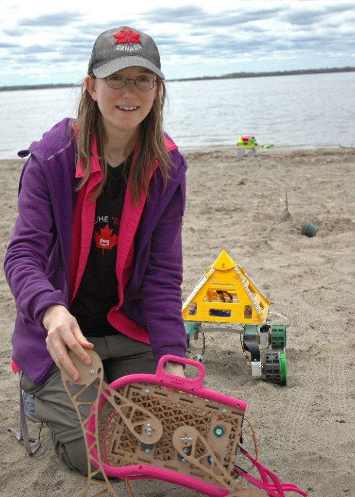 Erin demonstrates her prototype scissor lift beach cleaning bot with her two other bots behind her. Erin designed and constructed all three bots with the help of a 3D printer.