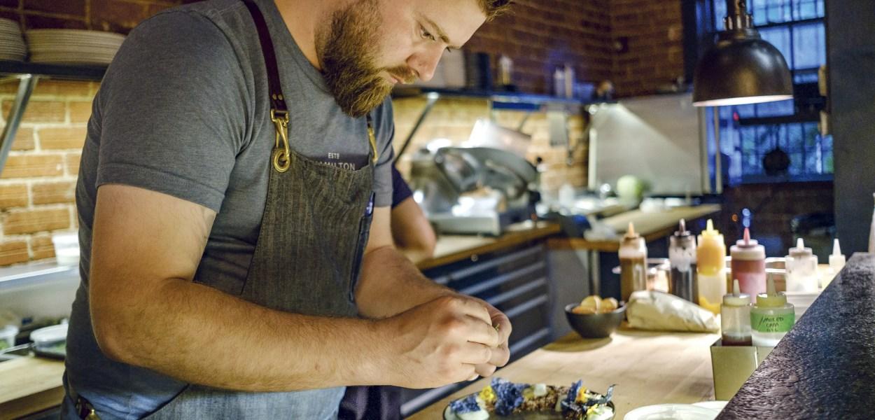Chec Justin Champagne of Bar Lupulus prepares a dish at his restaurant.
