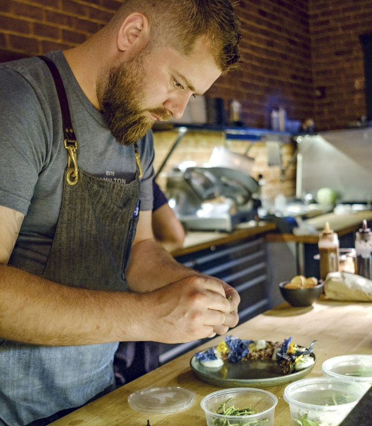 Chec Justin Champagne of Bar Lupulus prepares a dish at his restaurant.