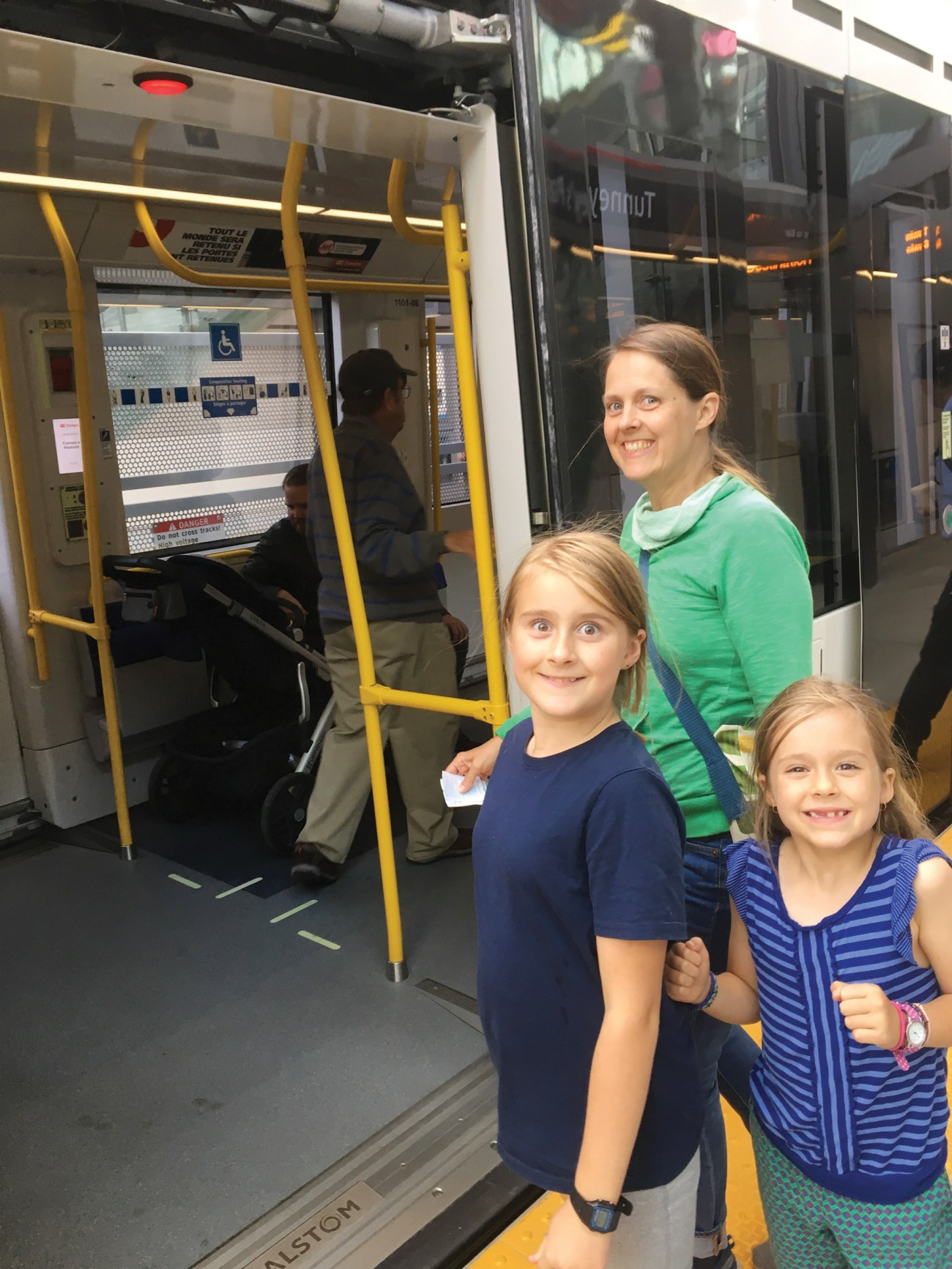 Mom and two kids get ready to board the new Ottawa LRT.