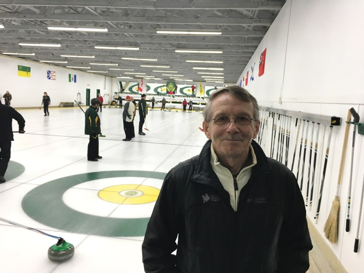 Greg Mathieu, Chair of the Granite Club's redevelopment committee, stands in front of a curling rink full of curlers.