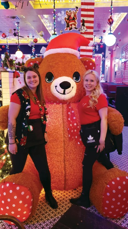 Savoy staff pose with a giant teddy bear as part of the decorations for Miracle Pop-up.