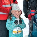 A young girl sips hot chocolate while getting her cheeks warmed up by a pair of hands.
