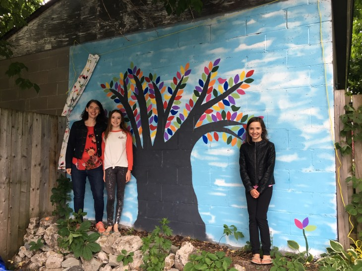 A photo of the Thomson family and their painted tree mural in Hintonburg.