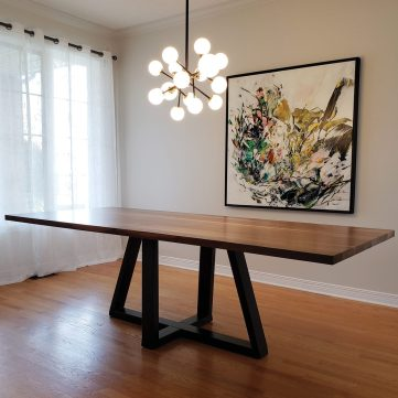 A photo of a walnut table with a geometric base made by Maker House.