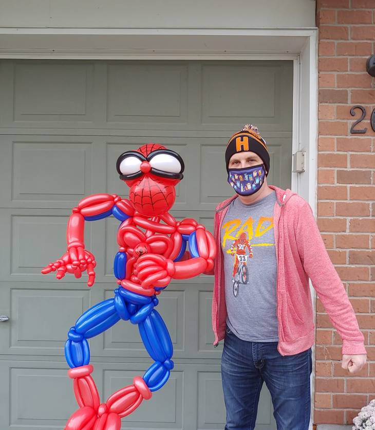 A photo of Brad the Balloon Guy holding a balloon artwork of Spiderman.