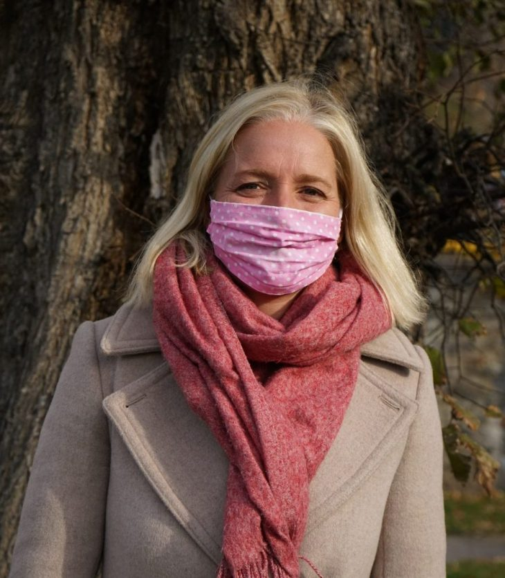 Catherine McKenna standing outside with a mask on in fall