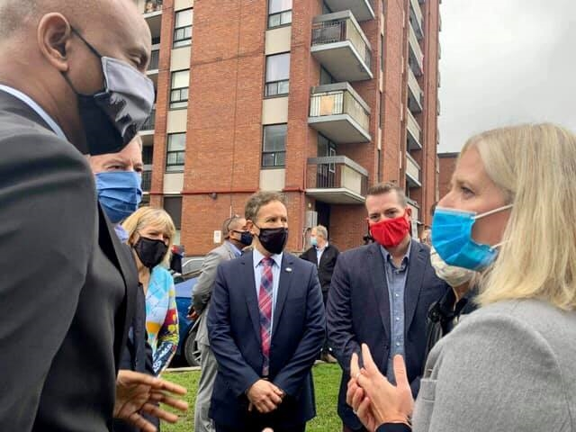 A photo of Minister McKenna, Minister Hussen, Stéphane Giguère outside the new affordable housing construction site in Ottawa.