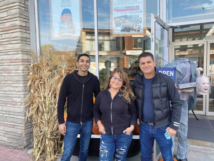 A photo of the three managers and owners of Noor Food Market outside their store in fall.