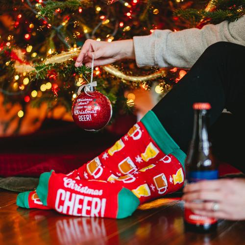 A hand holds a red ornament near a tree while the other hand holds a beer.