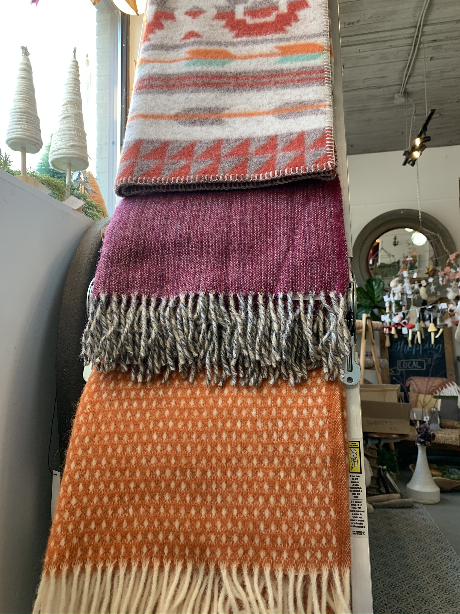 Three multicoloured wool blankets are folded over a ladder
