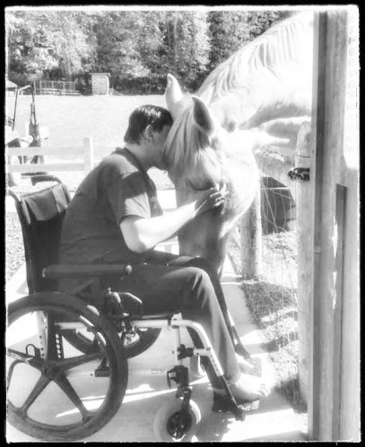 An individual in a wheel chair pets a horse in a black and white photo
