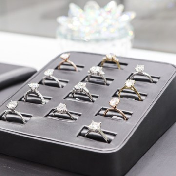 A black tray of moissanite rings is seen on a black countertop.