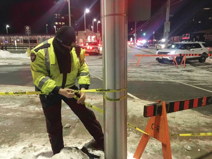 A police officer stands near a pole at the Westboro bus station and tapes off an accident scene