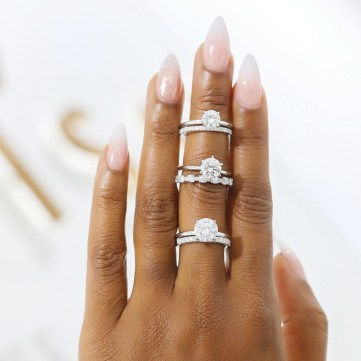 A hand wears three moissanite rings on its middle finger against a white background