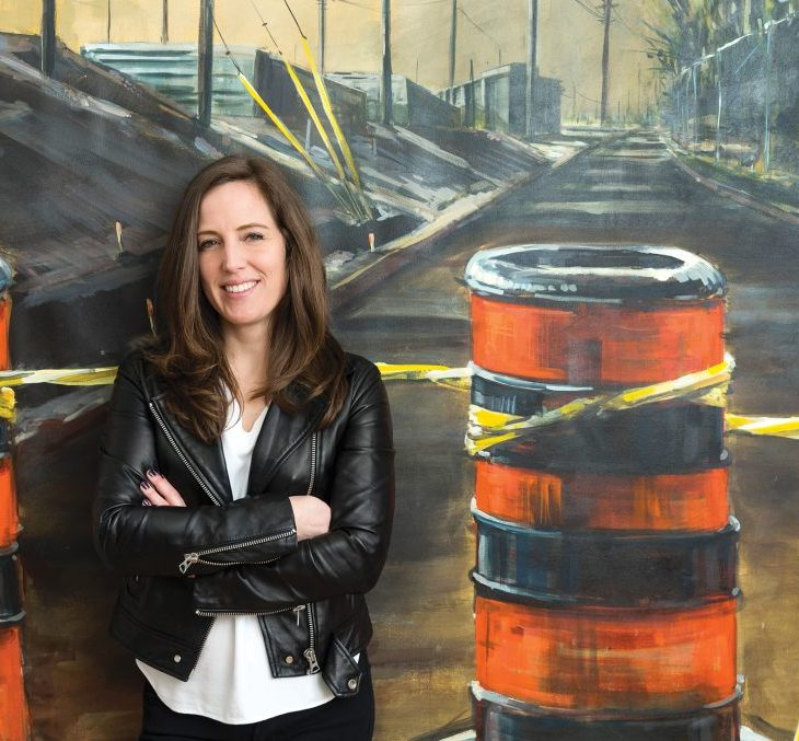 Eryn O'Neil stands with her arms crossed against one of her LRT artworks