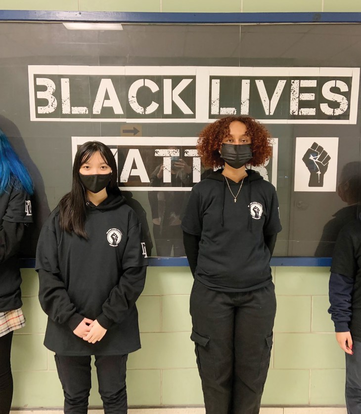 Four student stand in a row wearing black in front of a Black History month posterboard