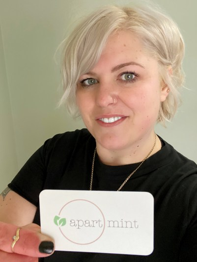 """A woman holds up a business card that says """"ApartMint"""" on it."""