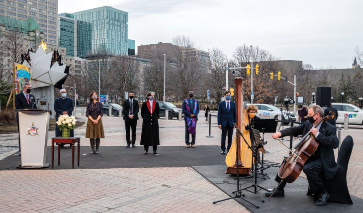 A group of people stand outside of city hall while two musicians play music on cellos on an overcast day in Ottawa