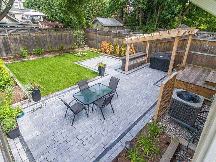 A backyard in Ottawa is seen with a table and chairs, manicured lawn and pergola.