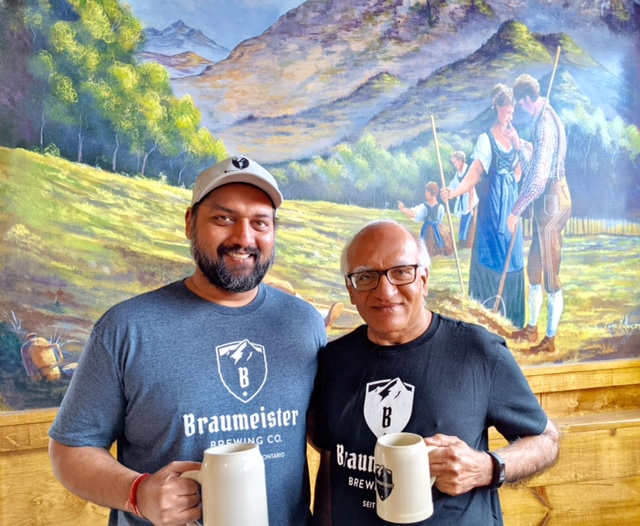 Rohit and Ravi Gupta stand side by side holding beer steins with a colourful mural behind them