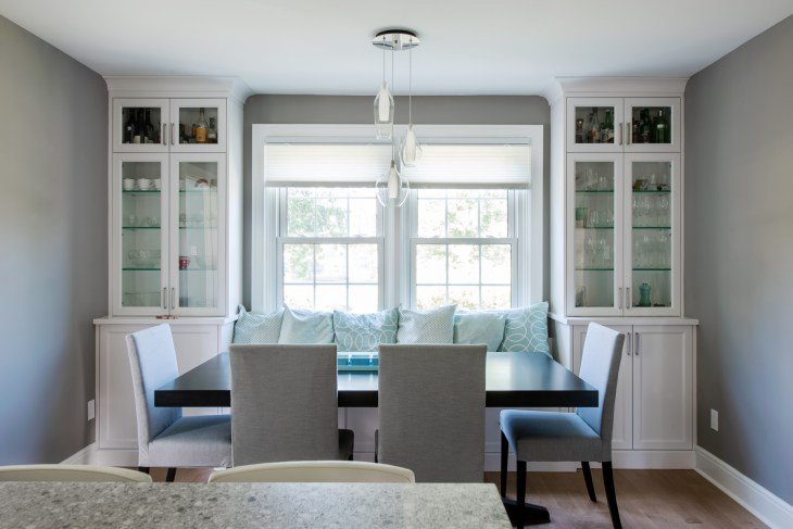 A renovated dining room is seen with white cabinets and a black table with white chairs