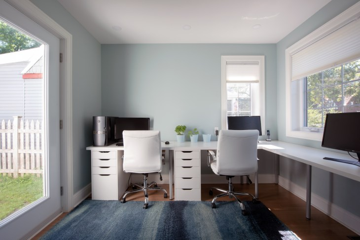 A desk with two stations is seen in a renovated home.