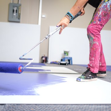 A close up of Claudia Salguero painting a white panel on the floor with blue paint