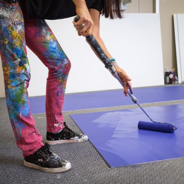 A close up of Claudia Salguero painting a blue panel on the floor