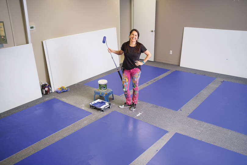 Claudia Salguero stands with a paint roller and blue panels around her on the floor in the middle of a studio space.