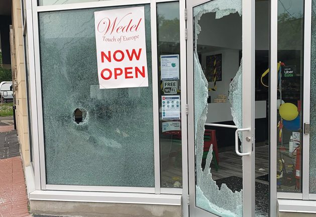 The outside of Wedel - Touch of Europe is seen with all its windows broken and damaged on the main level of the business