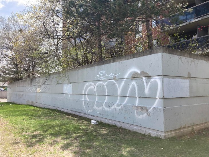 A grey cement wall with white graffiti is seen on a sunny day near Westboro Beach