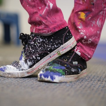 A close up of black sneakers and pink pants that are splattered with paint.