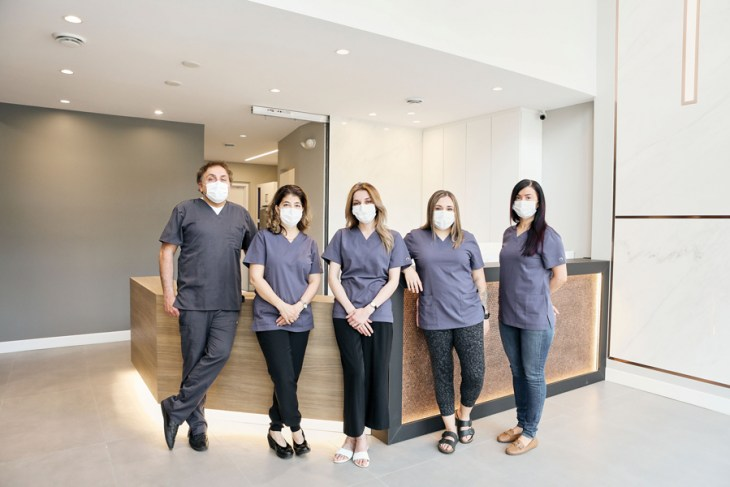 The team at W Dental Studio is seen wearing scrubs and masks standing in a line in the main lobby