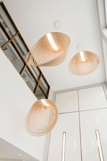 Three shell-shaped lights are seen hanging in a bright white lobby at W Dental Studio