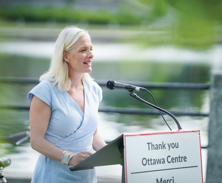 Catherine McKenna stands at a podium in Ottawa next to the Rideau Canal on a summer day