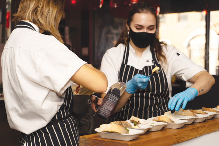 Two chefs prepare dishes at a Carefor event. Both are wearing black masks and blue gloves.