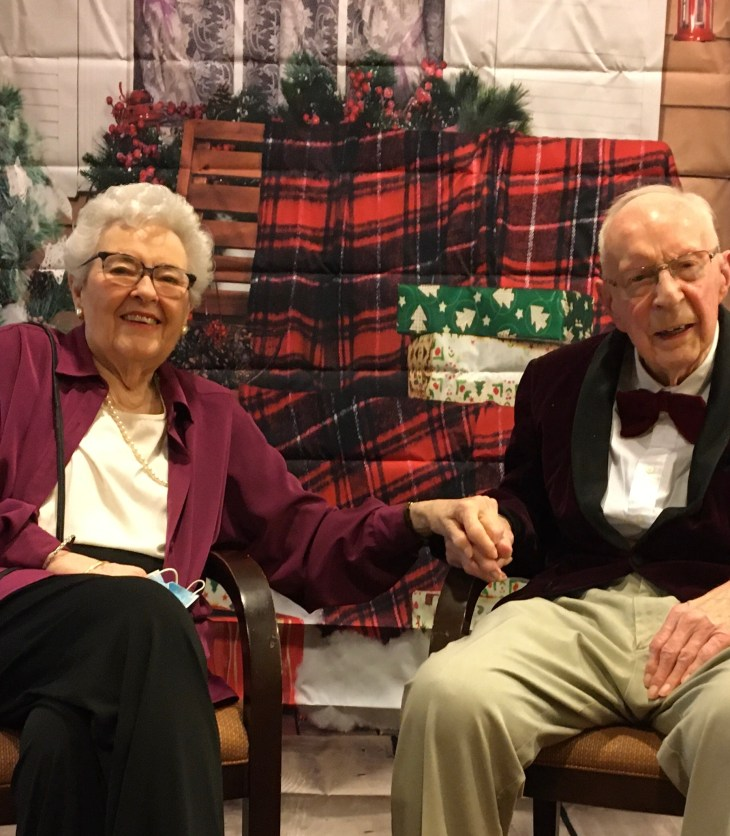 Two people sit in chairs at a retirement community with red plaid and holiday decor behind them.