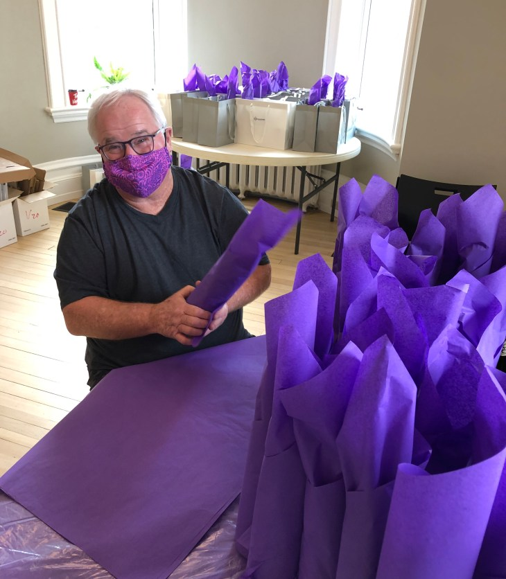 A man wearing a purple face mask fills a table of gift bags with bright purple tissue paper.