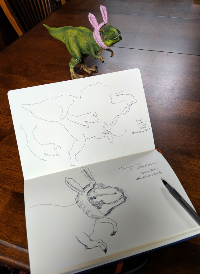 Sketchbook on table with a model dinosaur wearing bunny ears. Drawings by Kit Dunsmore.
