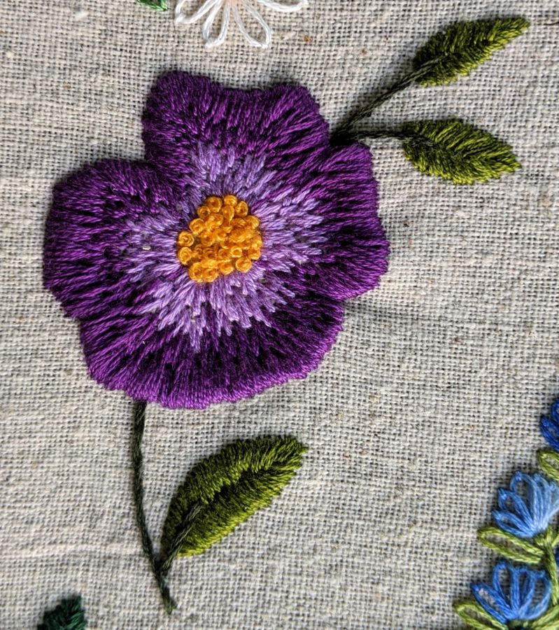 Close up of purple and gold embroidered flower by Kit Dunsmore