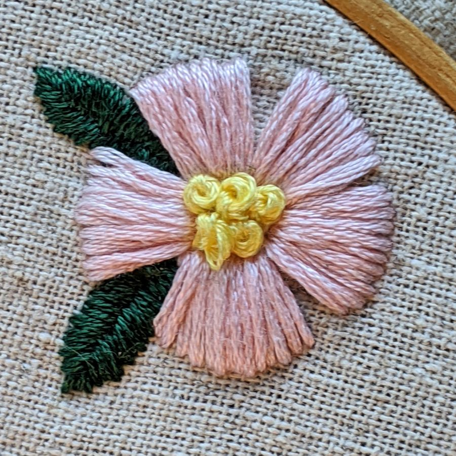 Close up of a pink embroidered flower by Kit Dunsmore